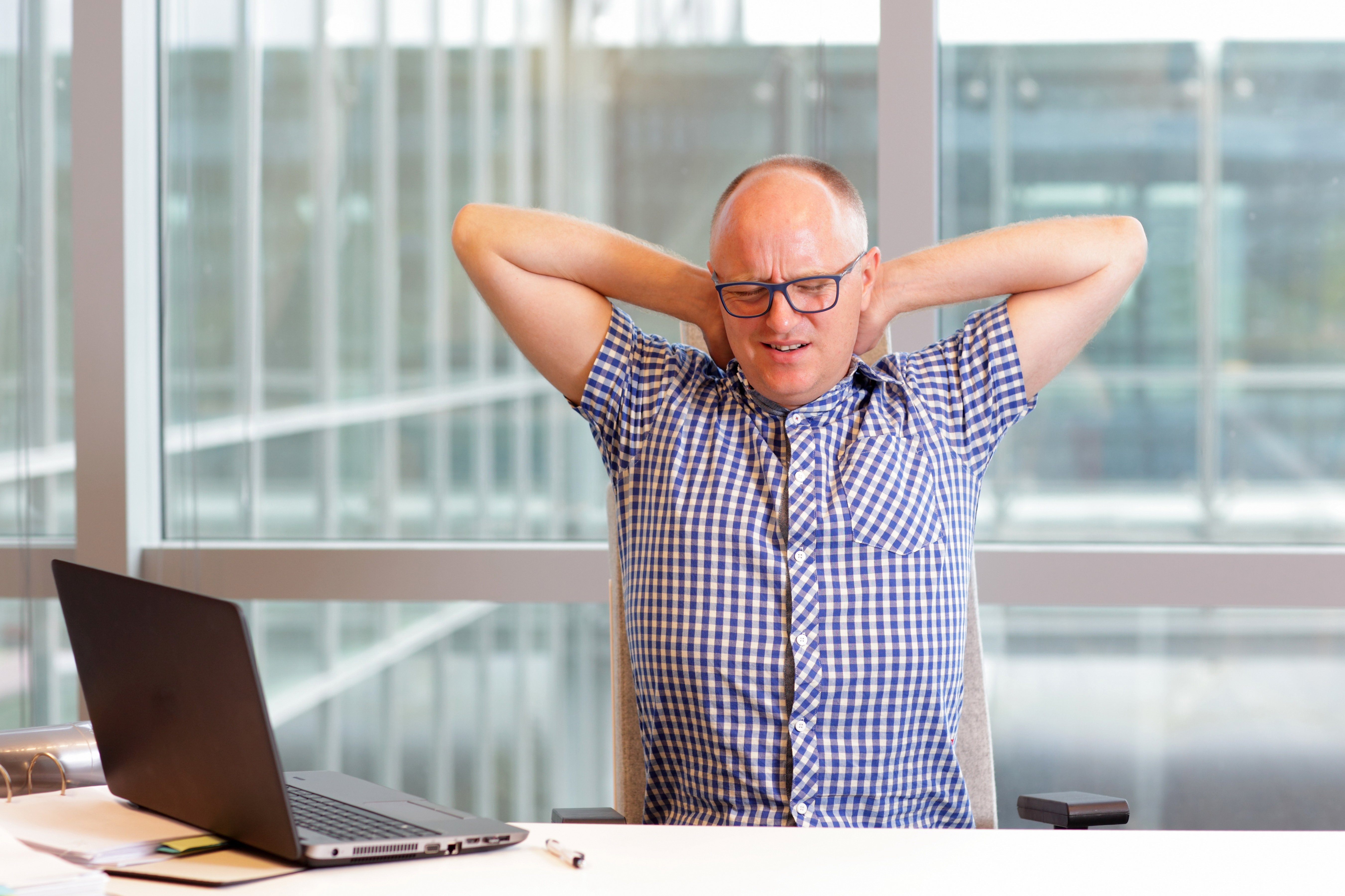 middle age man with pain in the neck stretching in office